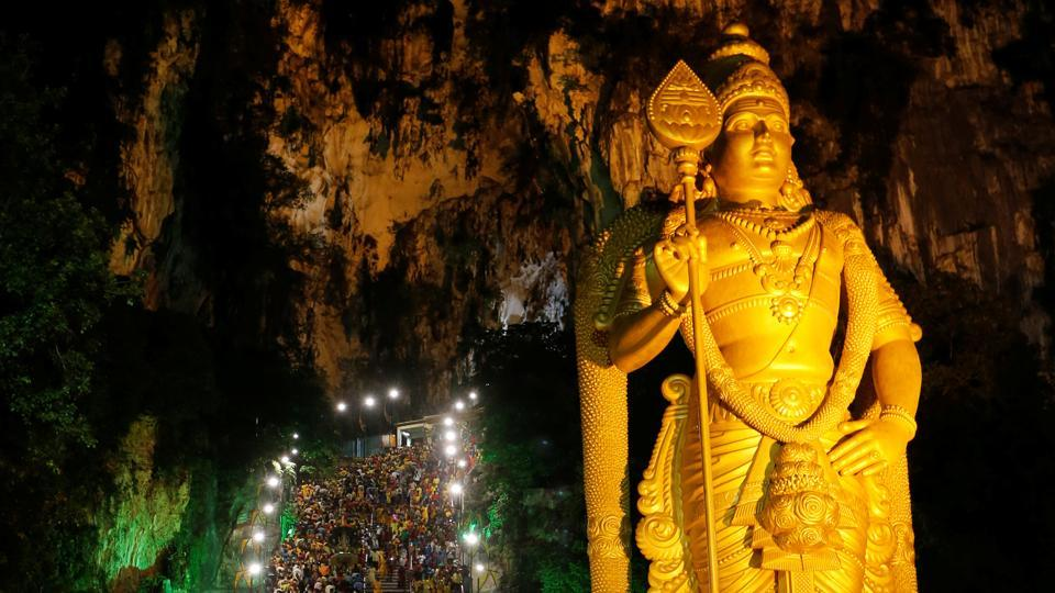 A large statue of Lord Murugan is illuminated as devotees climb the steps to Batu Caves in Kuala Lumpur, Malaysia on February 9, 2017.  (Lai Seng Sin / REUTERS)
