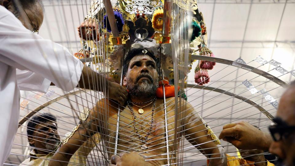 A devotee makes adjustments to his 'kavadi' in Singapore. The exact date of Thaipusam changes each year in the Gregorian calendar, as it is based on the full moon day in the month of Thai in the Hindu calendar. (Edgar Su  / REUTERS)