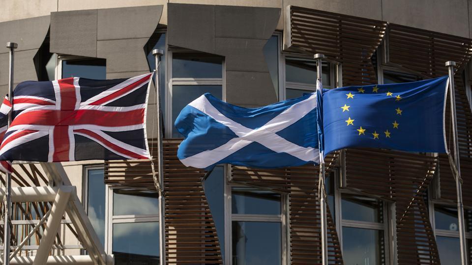 A Scottish Saltire (centre) flies between a Union flag (left) and a European Union flag.
