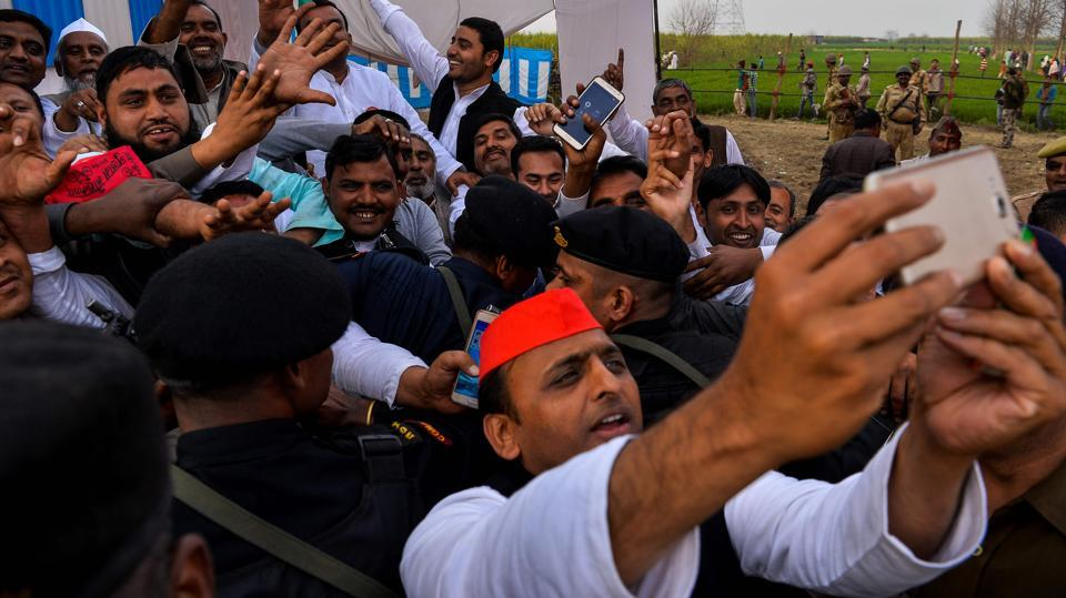 Uttar Pradesh state Chief Minister Akhilesh Yadav (C) takes a selfie  during a public rally at Sardhana in Meerut. March 11 is the day of reckoning for all parties, when election results will be declared.   (CHANDAN KHANNA / AFP)