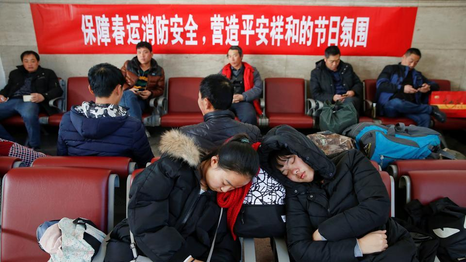 Passengers rest in front of a banner urging for fire protection during the Spring Festival at the departure hall of the Beijing Railway Station in central Beijing, China in January.