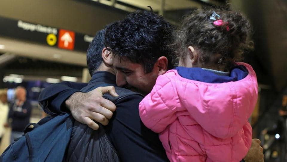 Iranian citizen and US green card holder Cyrus Khosravi (C) greets his brother, Hamidreza Khosravi (L), and niece, Dena Khosravi (R), 2, after they were detained for additional screening following their arrival to Seattle-Tacoma International Airport to visit Cyrus, during a pause in US President Donald Trump's travel ban in SeaTac, Washington.