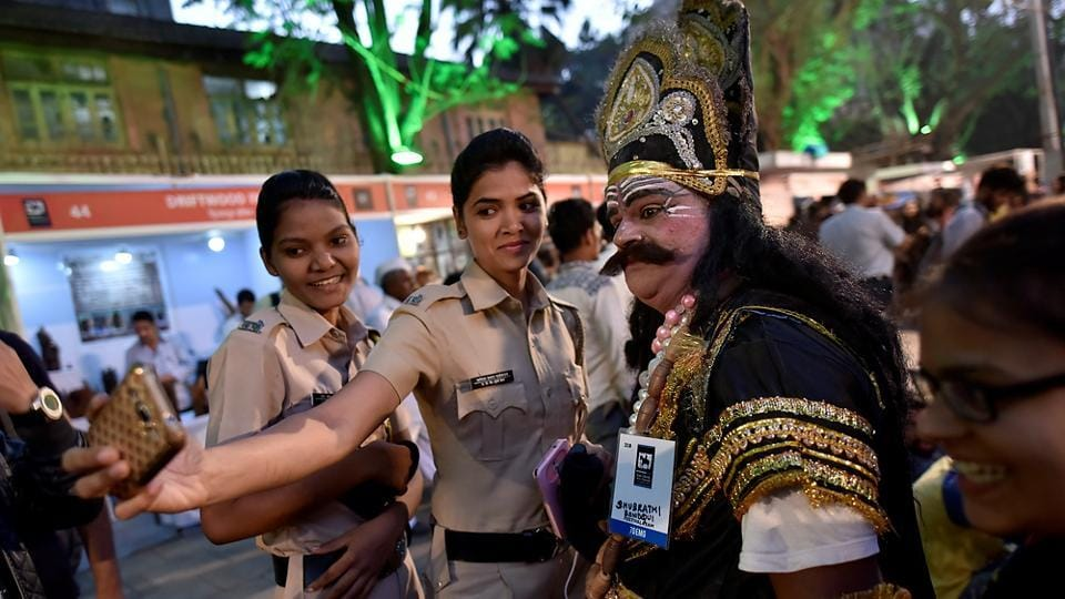 Policewomen take a photograph with a man dressed as a mythological figure. (Arijit Sen/HT PHOTO)