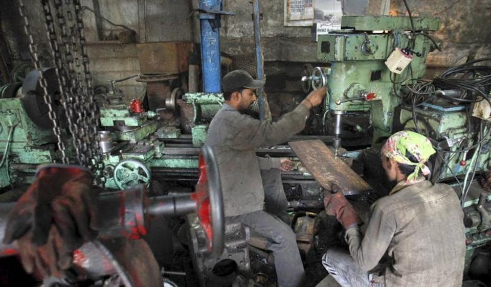 Workers make gear parts for cranes inside a workshop in Mumbai. Indian industrial output contracted to four-month low of 0.4% in December 2016.