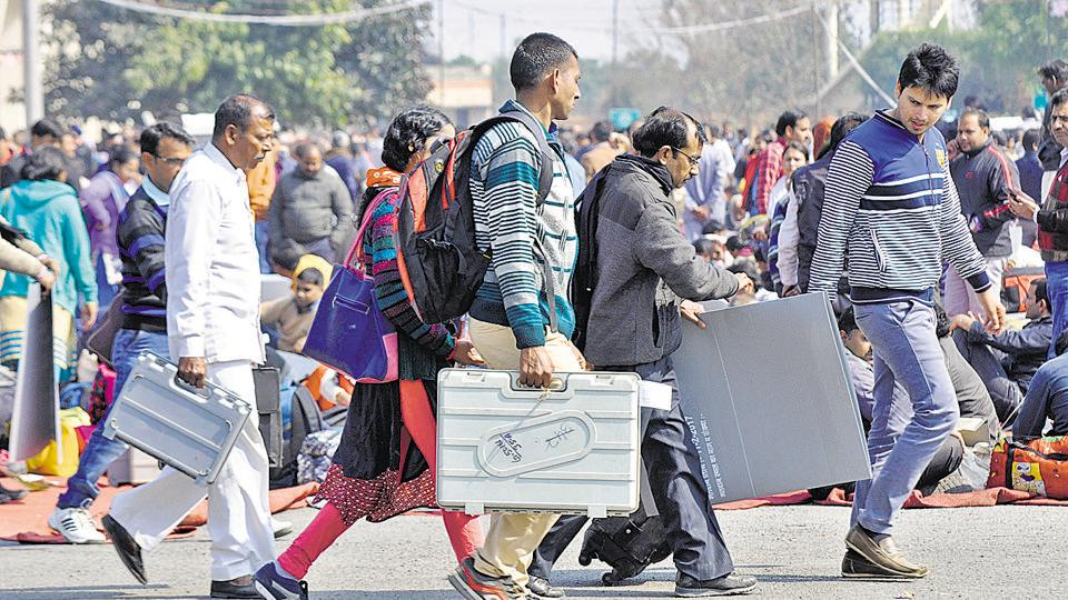 Block level officers carry electronic voting machines to their respective booths in Gautam Budh Nagar on Friday.