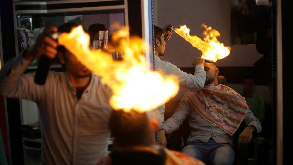 Palestinian barber Ramadan Odwan styles and straightens the hair of a customer with fire at his salon in Rafah, in the southern Gaza Strip.