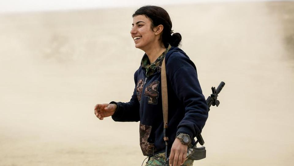 Doza Jiyan, a 21-year-old female Arab fighter among the Syrian Democratic Forces, made up of US-backed Kurdish and Arab fighters, walks carrying a machine gun near the village of al-Torshan, 20 km on the outskirts of Raqa on February 6, 2017.