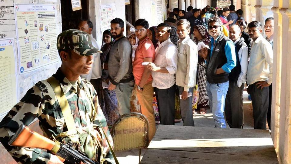 Voters wait in a queue to cast votes during the first phase of UP Assembly elections in Mathura on Saturday.