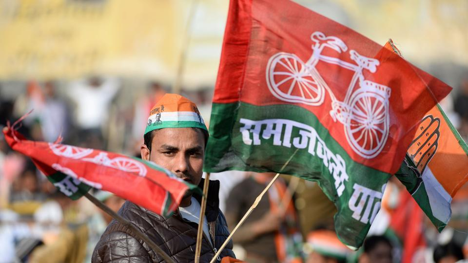 A supporter of the Congress and Samajwadi political parties waves party flags during an election rally by Congress Party leader Rahul Gandhi ahead of state assembly elections in Uttar Pradesh, in Ghaziabad on February 8, 2016.