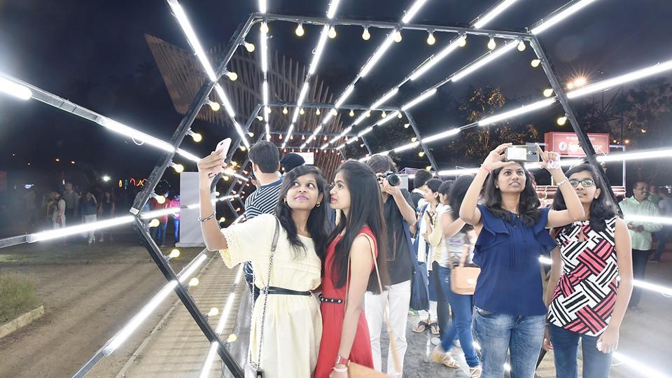 Youngsters stop by to admire an artwork of light. (Anshuman Poyrekar/HT PHOTO)
