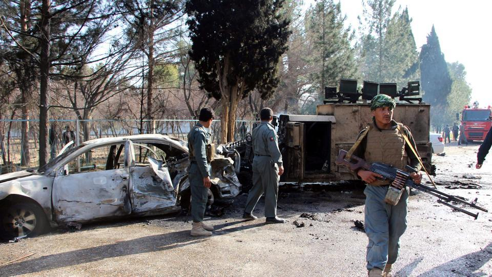 Afghan policemen inspect a damaged army vehicle after a suicide attack in Lashkargah, Helmand province, on February 11, 2017.