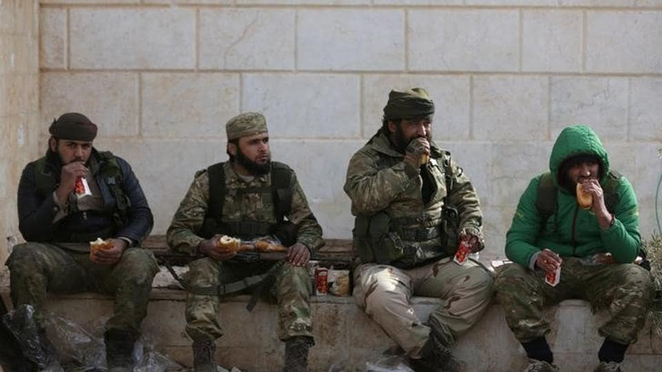 Rebel fighters eat while resting on the outskirts of the northern Syrian town of al-Bab, Syria.