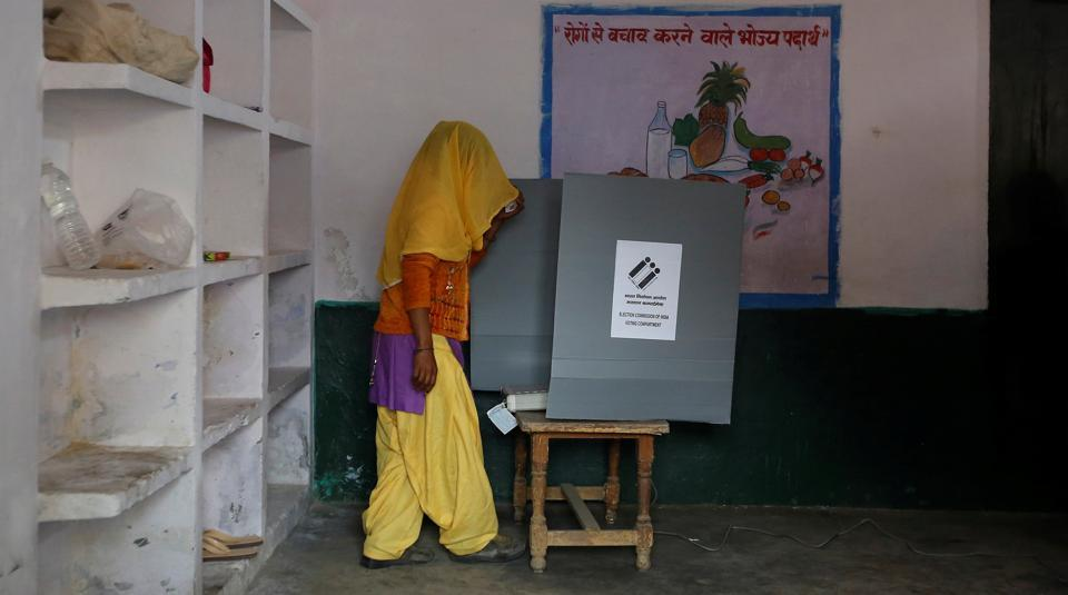 A woman looks at the electronic voting machine (EVM) before casting her vote inside a booth at a polling station during the Uttar Pradesh assembly election in Hapur on Feb 11.