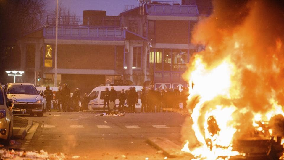 French police officers face protestors as a car burns in Bobigny, outside Paris, Saturday, Feb. 11.