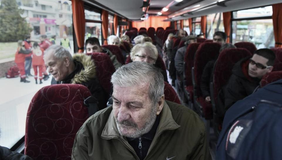 Residents of Kordelio district are seen aboard a bus after authorities ordered the evacuation of the area in order to defuse a 500-pound unexploded World War II bomb, in Thessaloniki, Greece Sunday, Feb 12.