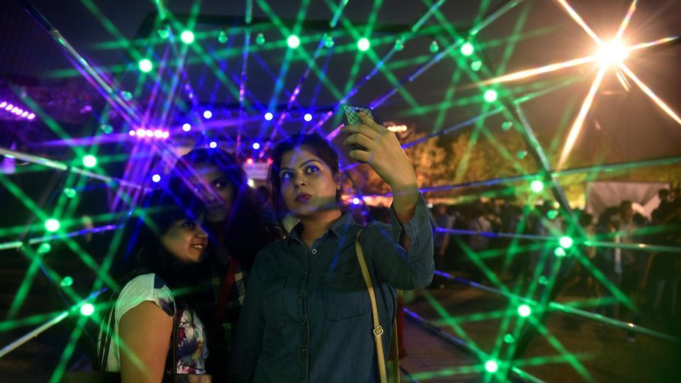People enjoy an artwork of light at the festival on Sunday. (Anshuman Poyrekar/HT PHOTO)