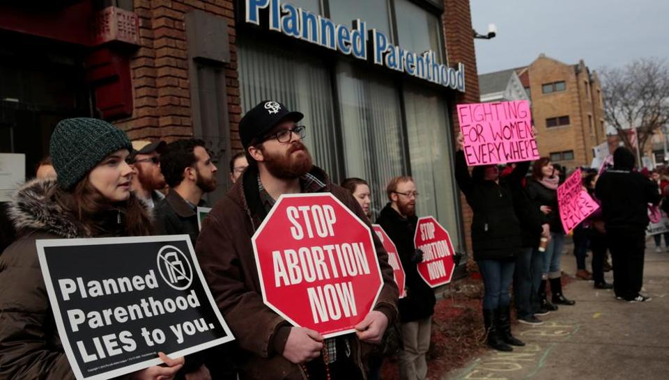 Anti-abortion activists (L) rally next to supporters of Planned Parenthood outside a Planned Parenthood clinic in Detroit, Michigan, U.S. February 11, 2017.