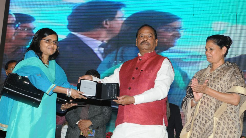 Chief MInister Raghubar Das distributing tabs among government officials during a function at HEC stadium in Ranchi on Saturday