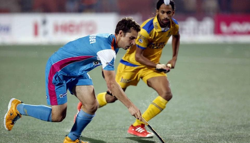 An Uttar Pradesh Wizards player (in blue) tries to dribble past a Jaypee Punjab Warriors player in the Hockey India League match in Chandigarh on Monday.