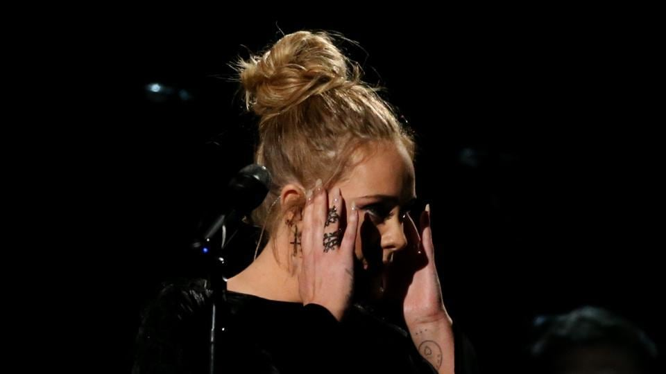 Singer Adele reacts after making a mistake and starting over while performing a tribute to the late George Michael.