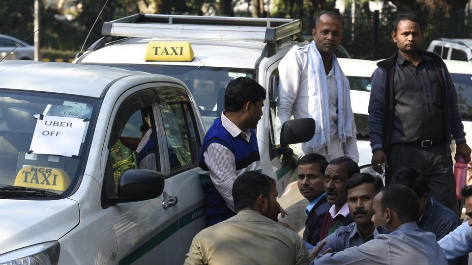Ola and Uber taxi drivers sit near their cars during the ongoing strike against withdrawal of incentives, in New Delhi on Saturday.