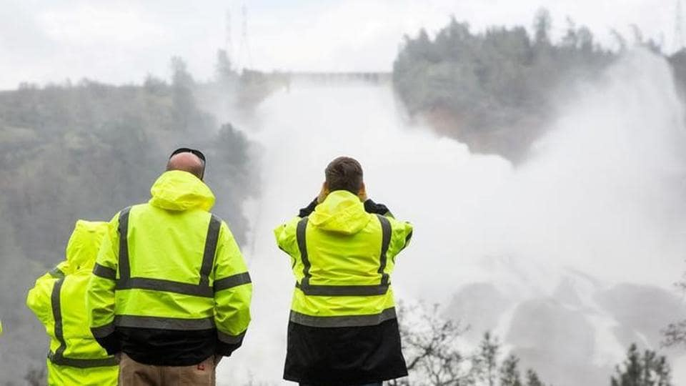California Department of Water Resources personnel monitor water flowing through a damaged spillway on the Oroville Dam.