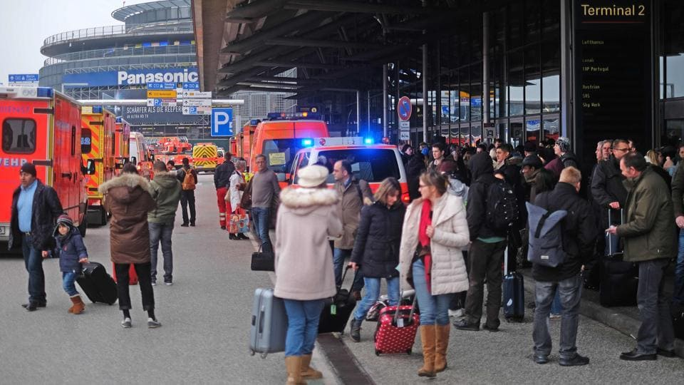 Firefighters with multiple vehicles stand in front of Hamburg airport as passengers leave the terminal on Sunday in Hamburg, northern Germany, as emergency services evacuated the airport.
