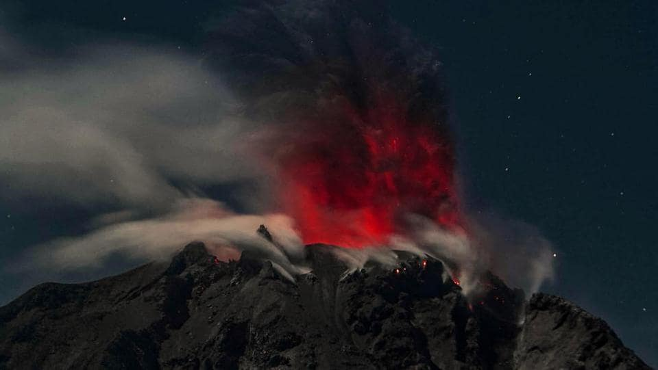 In this timed-exposure night photo taken early on February 12, 2017, Mount Sinabung volcano spews reddish smoke and ash, as seen from the Karo district in North Sumatra province.  (AFP)