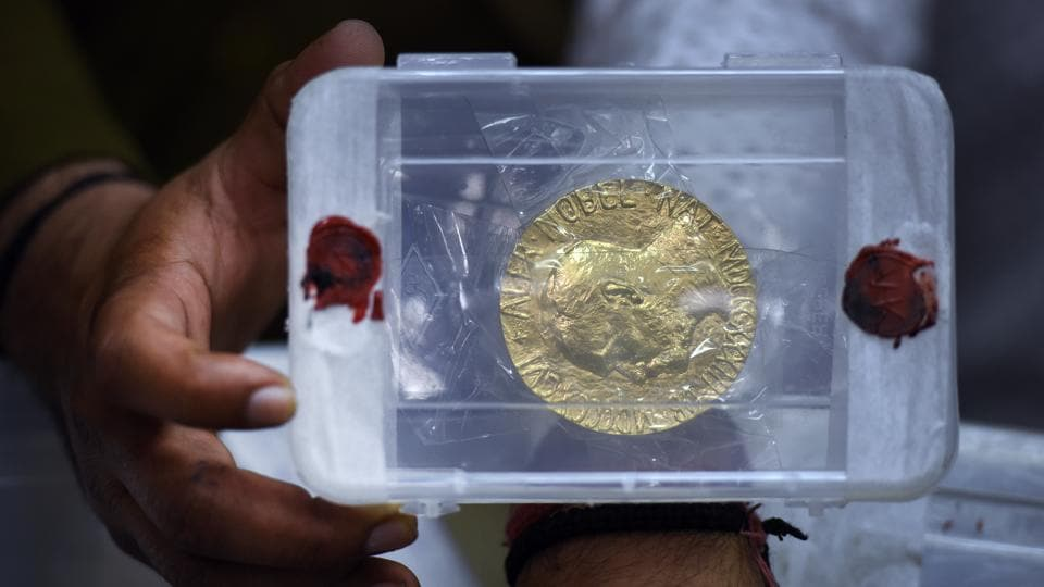A cop showing a replica of Kailash Satyarthi's Nobel prize medal recovered from the burglars in New Delhi on Sunday.