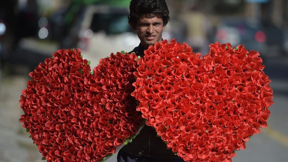 A Pakistani vendor carries heart-shaped bouquets for sale ahead of Valentine's Day along a street in Islamabad on February 13, 2017.