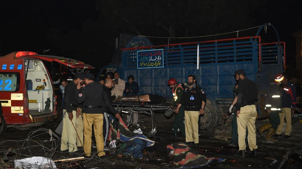 Pakistani policemen and volunteers move the bodies of victims at the site of a bomb explosion in Lahore on February 13, 2017.