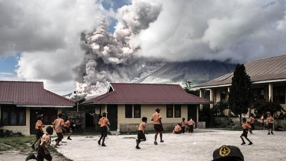 Elementary school children play outside of their classrooms as Mount Sinabung volcano spews thick volcanic ash as seen from Karo, North Sumatra province, on February 10, 2017. (AFP Photo)