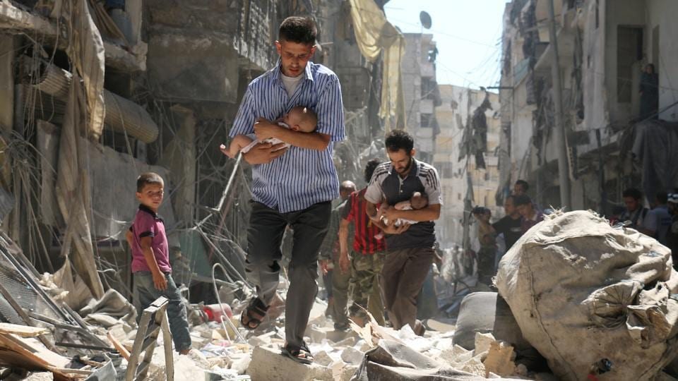 Spot news, second prize: Syrian men carrying babies make their way through the rubble of destroyed buildings following a reported airstrike on the rebel-held Salihin neighborhood of Aleppo.  (Ameer Alhalbi )
