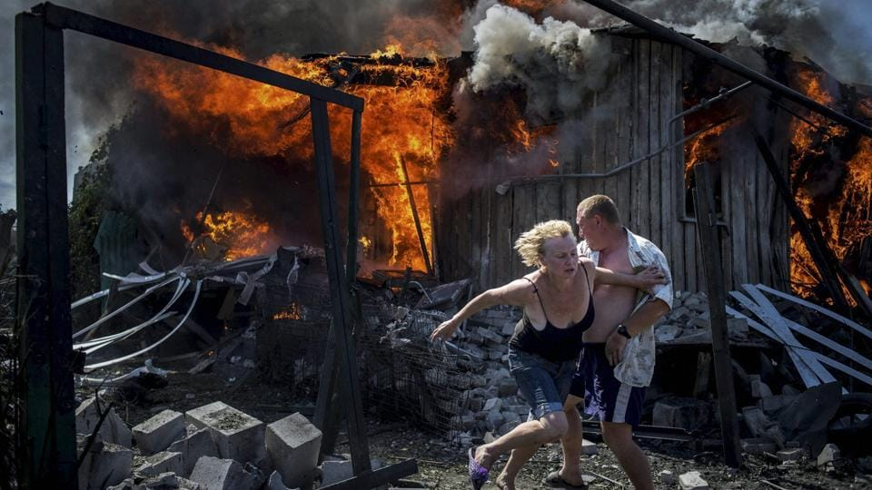 Long-Term Projects, first prize stories: Civilians escape from a fire at a house destroyed by an air attack in the Luhanskaya village.  (Valery Melnikov / AP Photo)