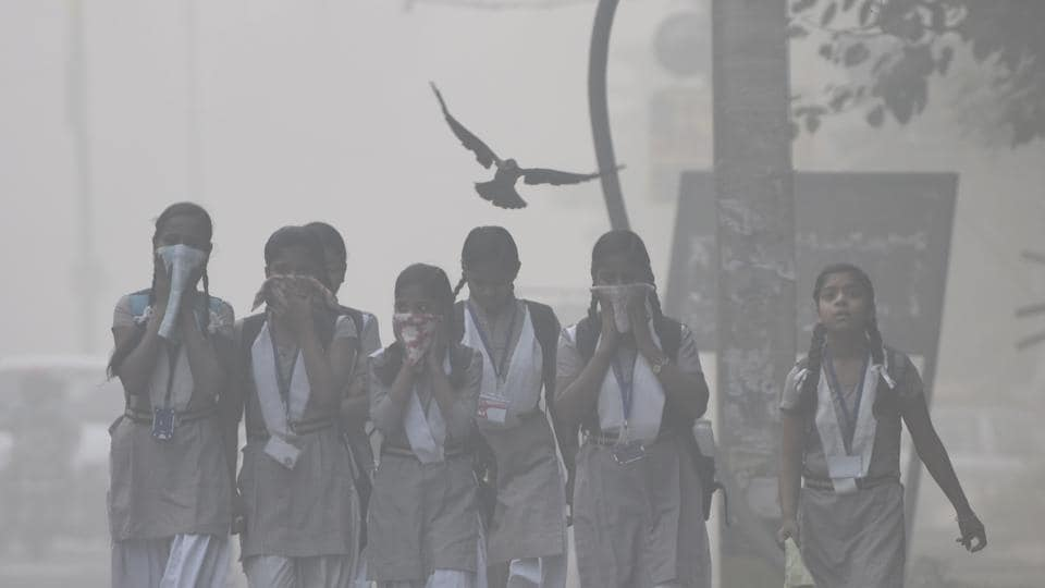 Students cover faces amid heavy smog in New Delhi.