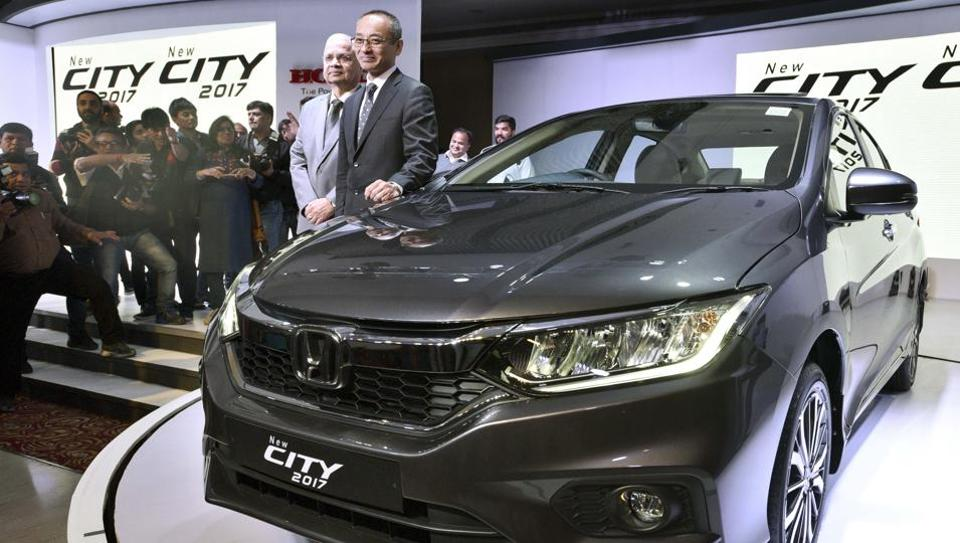 Chief Executive and President of Honda Cars India Ltd, Yoichiro Ueno with SVP & Director Honda Cars India Ltd, Raman Kumar Sharma (L) pose for photographers during the launch of Honda City 2017 car in New Delhi.  (Mohd Zakir/HT PHOTO)