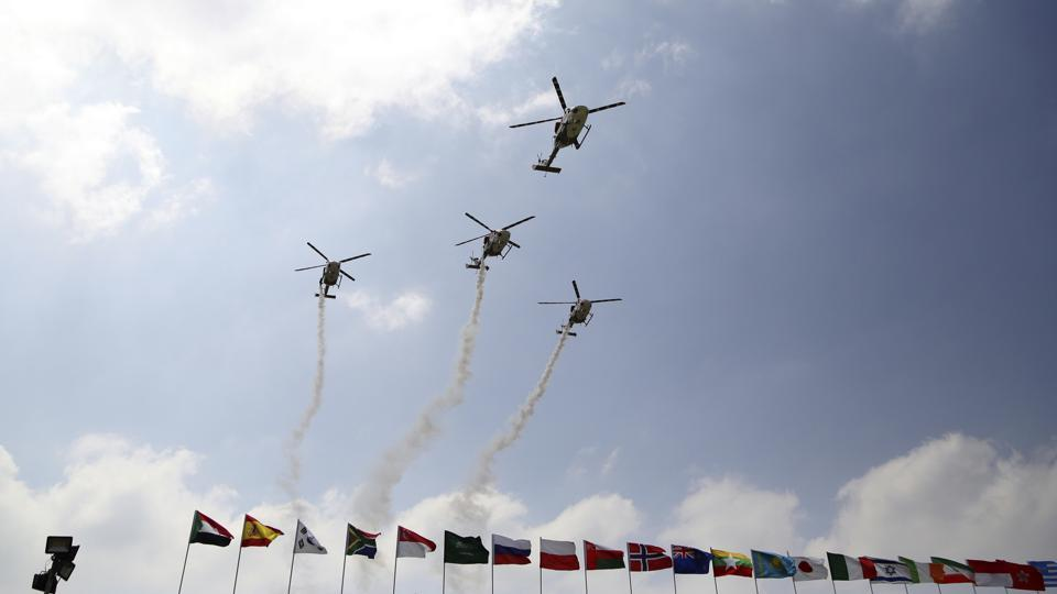 Indigenously manufactured Indian Air Force Dhruv helicopters fly over flags of participating countries at the opening ceremony of Aero India 2017 at Yelahanka air base in Bangalore. (AP)