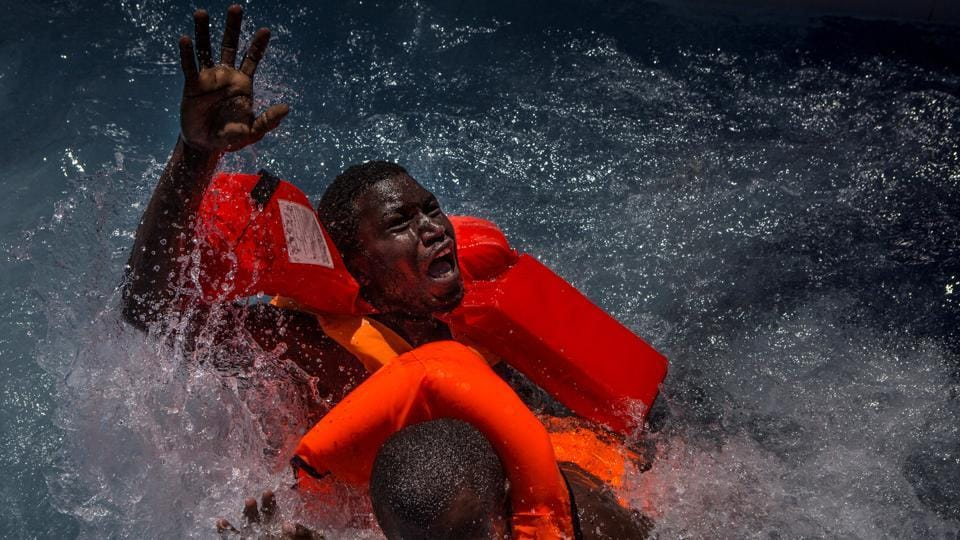 Spot news, second prize: Two men panic and struggle in water during their rescue. Their rubber boat was in distress and deflating quickly on one side, tipping many migrants in the water. They were quickly reached by rescue swimmers and brought to safety.  (Mathieu Willcocks)