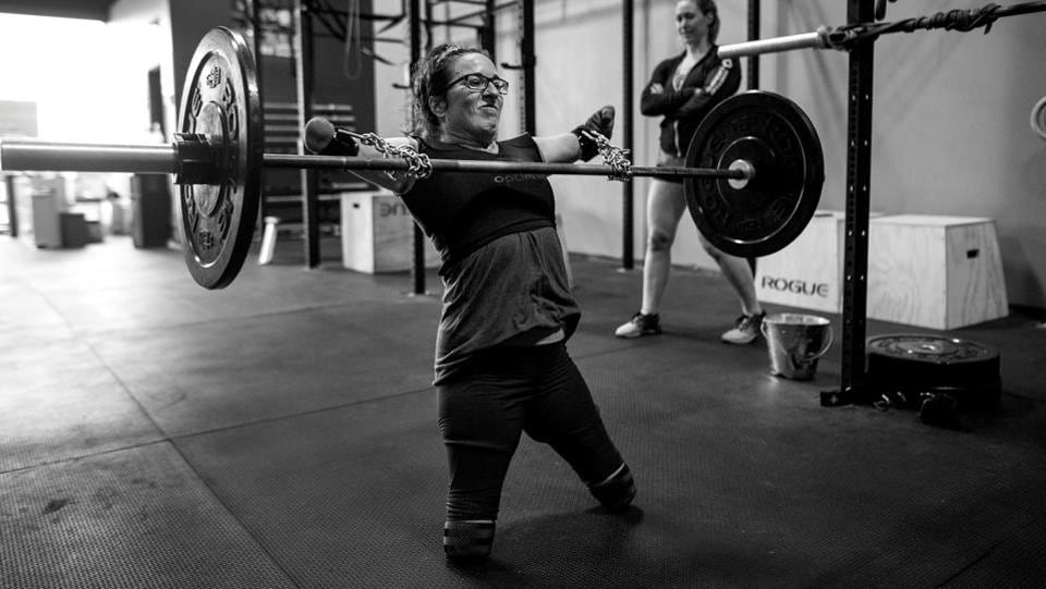 Sports, third prize stories: With the aid of chains purchased at the hardware store and deadlift straps, Lindsay performs cleans under the watchful eye of her coach Jenny Jeffries. (Darren Calabrese )
