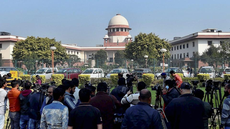 People gather outside the Supreme Court building in New Delhi on Tuesday.