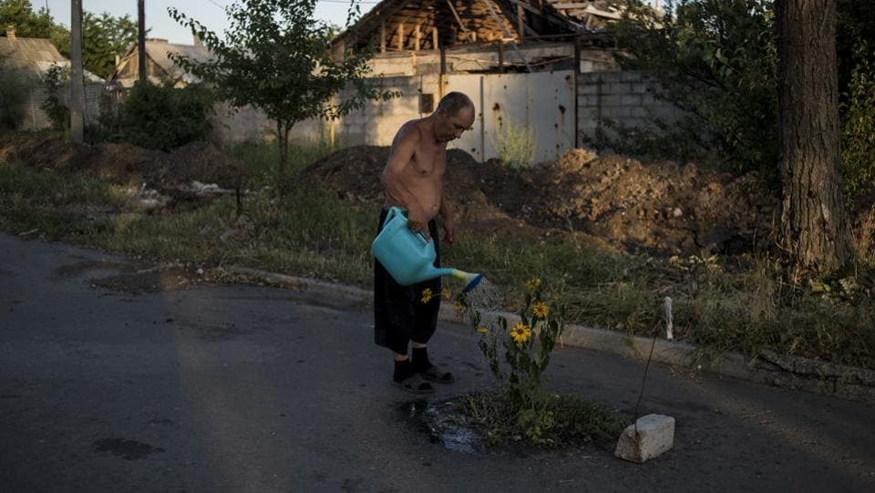 Long Term project, first prize: A man waters flowers on a street in the destroyed village of Spartak, Ukraine. (Valery Melnikov)
