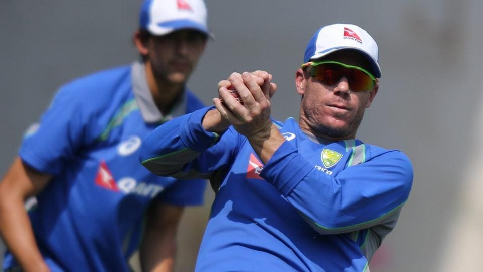 Australia's David catches a ball as Mitchell Starc looks on during their training in Mumbai on Wednesday.