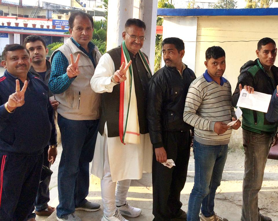 BJP leader Ganesh Joshi (centre) stand in a queue to cast his vote in Dehradun.