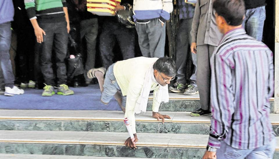 In absence of a ramp, a disabled man stumbles while climbing down the stairs after a disabled people felicitation ceremony in Jaipur. Leave aside displaying sensitivity for the disabled ,  most public places are inaccessible and have no designated spaces for wheelchair users.