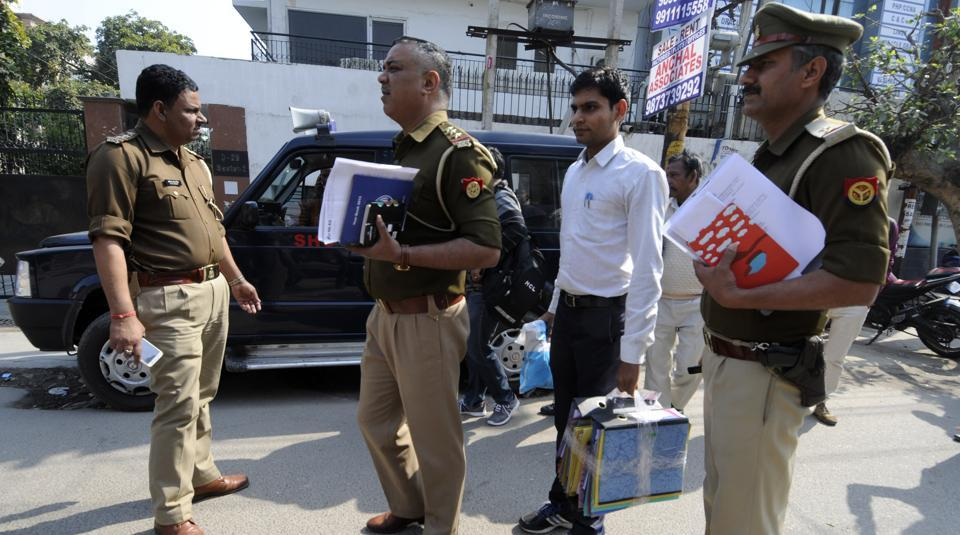 Noida police officers come out after sealing the sector 2 office of Webwork Trade Links Pvt Limited — an online social trading company that is being investigated for allegedly duping thousands of investors — on Wednesday.