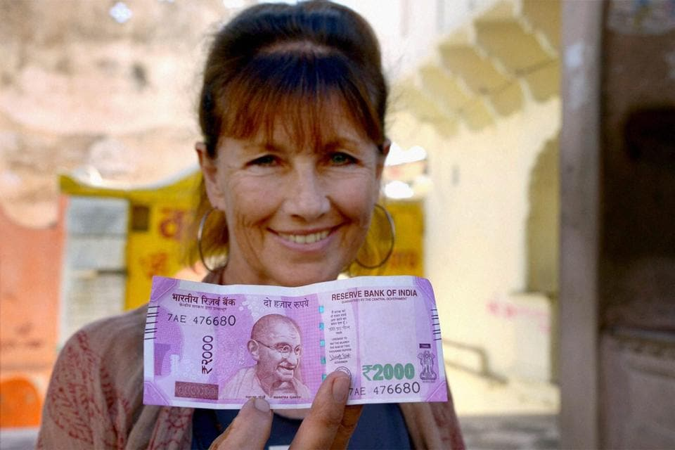Pushkar: A foreign tourist shows Rs 2000 note at Pushkar, Rajasthan on Wednesday. PTI Photo (PTI11_23_2016_000242B)