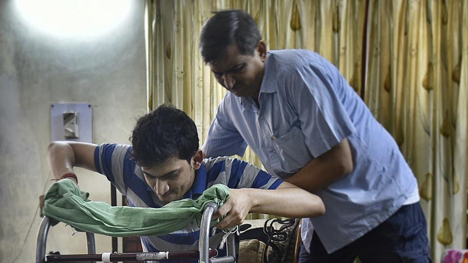 Ravi Rai, the patient who was wrongly operated, takes his father's help to move.