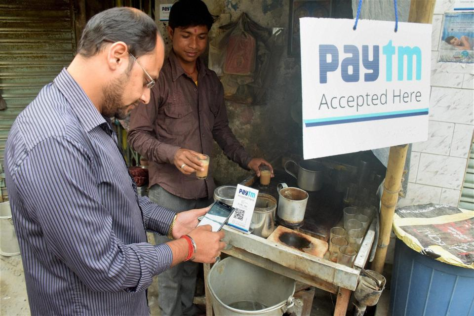 A person pays his bill at a tea stall using Paytm app at Balurghat in West Bengal.