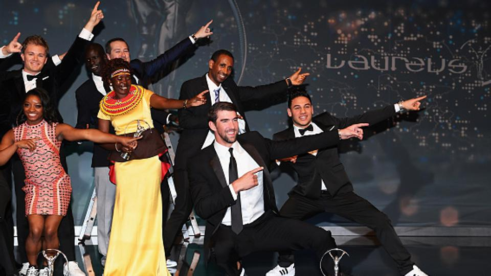 Michael Phelps of the US, winner of the Laureus World Comeback of the Year, performs with other winners, Usain Bolt's trademark celebratory move during the Laureus World Sports Awards function in Monaco on Tuesday. Bolt won his fourth Laureus Sportsman of the Year award while Simone Biles (left) won the Sportswoman of the Year crown.  (Getty Images for Laureus)