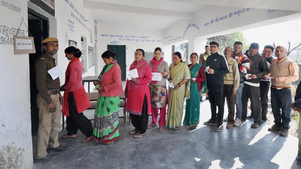 Women voters show voter ID cards as they stand in queue to cast their votes at a polling booth in Raipur constituency in Dehradun on Wednesday.